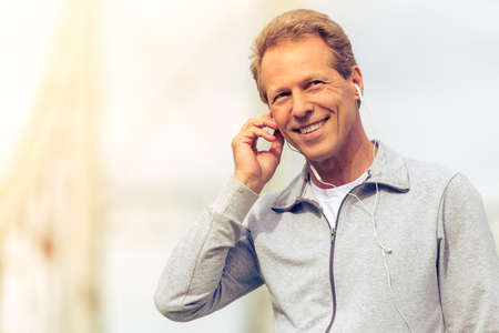 sports uniform: Portrait of handsome middle aged man in sports uniform and headphones smiling during morning run Stock Photo