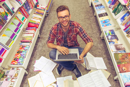 scientific literature: High angle view of handsome student using a laptop, looking at camera and smiling while sitting on the floor among open books in the bookshop