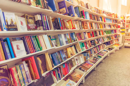 現代都市の本屋の棚の上に横たわるさまざまなカラフルな書籍の行