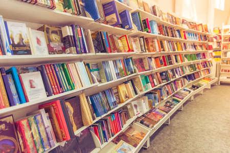 Filas de diferentes libros de colores acostado en los estantes de la librería urbana moderna Foto de archivo - 57557055