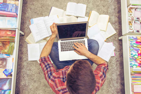 scientific literature: Top view of handsome student studying using a laptop while sitting on the floor among open books in the bookshop Stock Photo