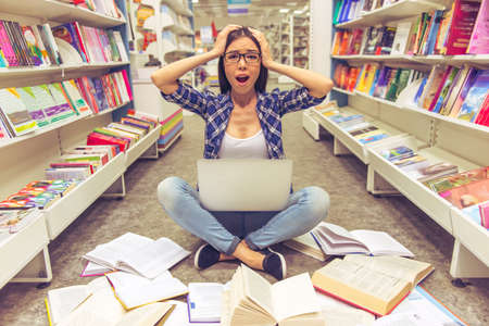 scientific literature: Attractive girl in eyeglasses has stress, using a laptop and keeping hands on head while sitting on the floor among open books in the bookshop Stock Photo