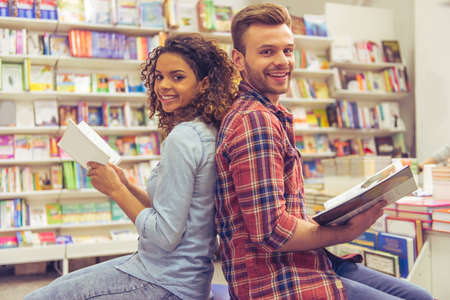 scientific literature: Handsome guy and beautiful girl are reading books, looking at camera and smiling while sitting back to back in the book shop
