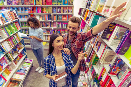 acquaintance: Attractive girl is smiling and asking handsome guy to take book from upper shelf in the bookshop, another girl in the background Stock Photo