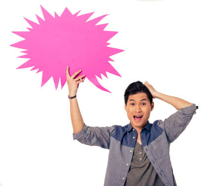 Handsome young Chinese man is holding speech bubble, looking at camera and showing confusion, isolated on white background