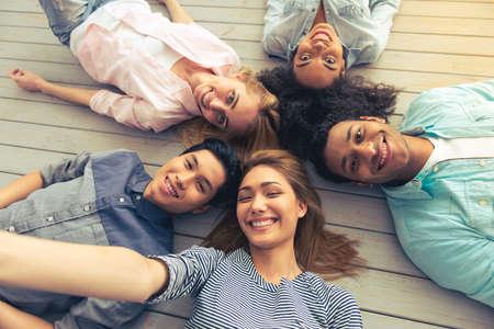 Bovenaanzicht van jonge mensen van verschillende nationaliteiten te kijken naar de camera en glimlachen terwijl het liggen op de vloer