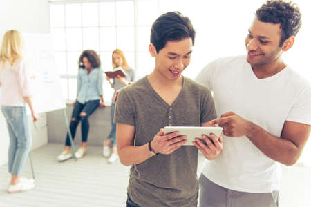 asian afro: Handsome Asian and Afro American guys are using tablet and smiling, in the background their colleagues are discussing business affairs