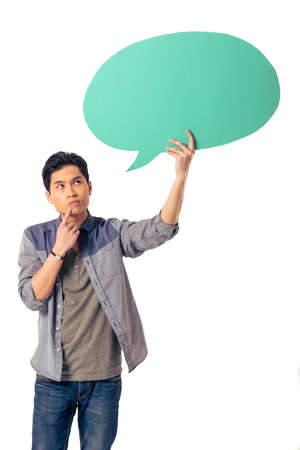 Handsome pensive young Chinese man is holding speech bubble, looking at it and thinking, isolated on white background