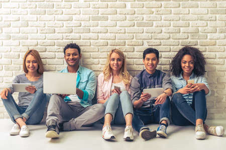 Beautiful young people of different nationalities are using gadgets, looking at camera and smiling, sitting against white brick wall