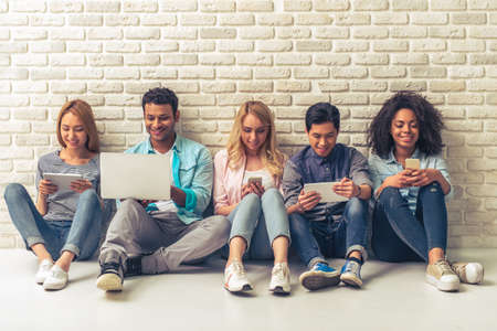 Beautiful young people of different nationalities are using gadgets and smiling, sitting against white brick wall