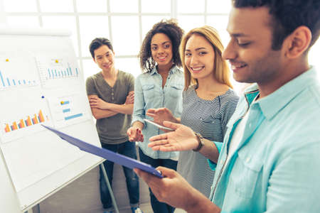 nationalities: Young people of different nationalities are discussing business affairs, examining graphs and smiling Stock Photo