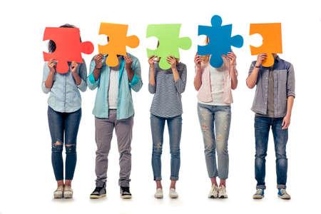 さまざまな国籍の若者は、パズル、白い背景で隔離のカラフルなピース裏の顔を隠しています。 写真素材