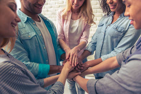circulo de personas: Cropped image of young people of different nationalities holding hands together and smiling