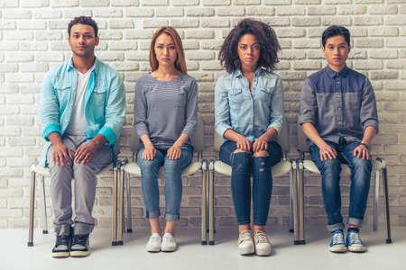 Jonge mensen van verschillende nationaliteiten zijn op zoek naar de camera tijdens de vergadering met de handen op de knieën in een rij
