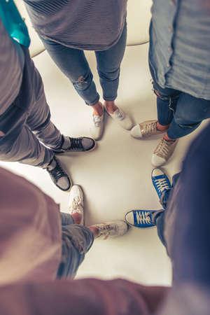 circulo de personas: Vista superior de las piernas de los jóvenes en los zapatos casuales de pie en círculo