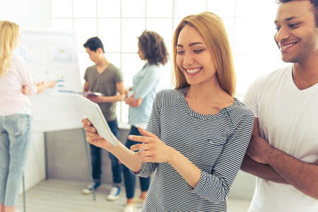 asian afro: Beautiful Asian girl and Afro American guy are using tablet and smiling, in the background their colleagues are discussing business affairs