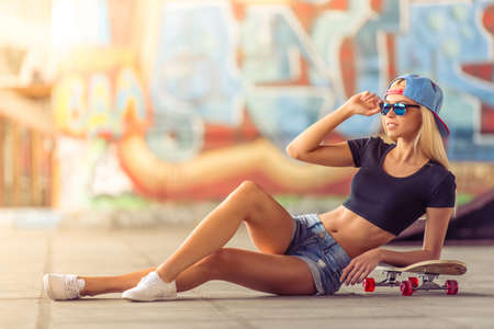 Beautiful blonde girl in glasses and cap is looking away and leaning on her skateboard while sitting on the ground in skate park Stock Photo - 57564995