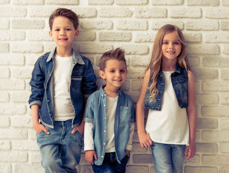 Cute little kids in stylish jeans clothes are looking at camera and smiling, standing against white brick wall