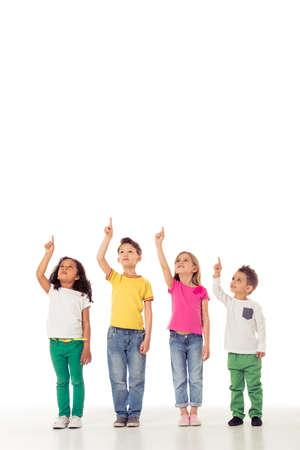 petit bonhomme: Portrait en pied de petits enfants mignons dans des vêtements décontractés à la recherche et pointant vers le haut, isolé sur un fond blanc