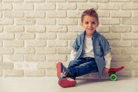 Cute stylish little boy in jeans is looking at camera and smiling, sitting on his skateboard against white brick wall