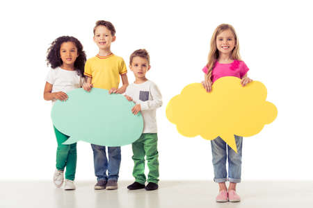 bubble talk: Full length portrait of cute little kids in casual clothes holding speech bubbles, looking at camera and smiling, isolated on a white background Stock Photo