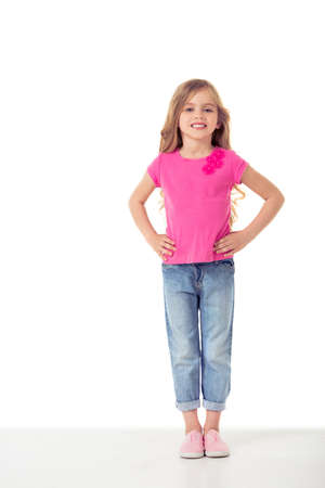 akimbo: Full length portrait of cute little girl in casual clothes looking at camera and smiling while standing akimbo, isolated on a white background