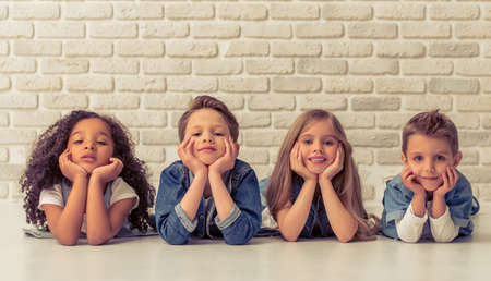 Cute little kids in stylish jeans clothes are leaning on their hands, looking at camera and smiling, lying on the floor against white brick wall