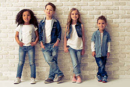 Full length portrait of cute little kids in stylish jeans clothes looking at camera and smiling, standing against white brick wall