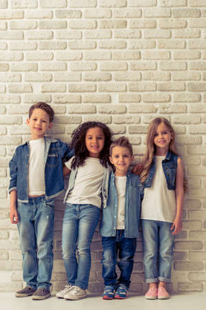 Full length portrait of cute little kids in stylish jeans clothes hugging, looking at camera and smiling, standing against white brick wall