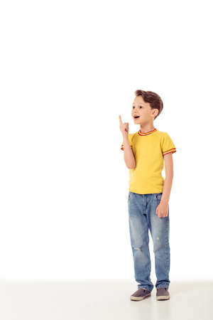 beautiful boy: Funny little boy in casual clothes is pointing up, looking away and smiling, isolated on a white background
