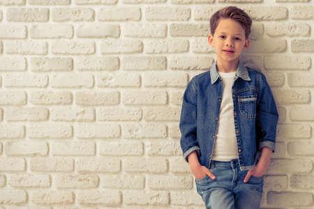 niño de pie: niño pequeño con estilo en ropa de jeans está mirando la cámara y sonriente, de pie con las manos en los bolsillos contra el muro de ladrillo blanco