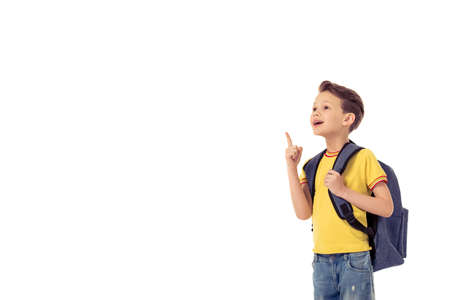 beautiful boy: Funny little boy with school backpack is smiling, looking and pointing upward, isolated on a white background