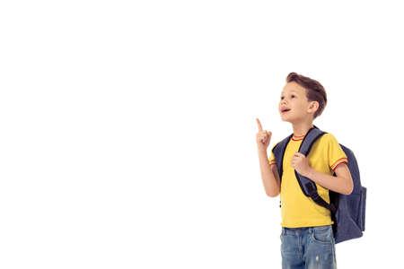 niño con mochila: Niño pequeño divertido con mochila escolar está sonriendo, mirando y apuntando hacia arriba, aislado en un fondo blanco
