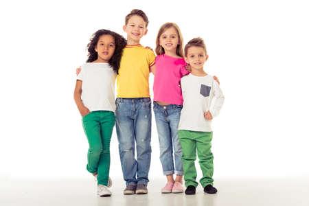 カジュアルな服でかわいい小さな子供がカメラを見て、腕をお互い、白い背景で隔離の周り立っている笑顔