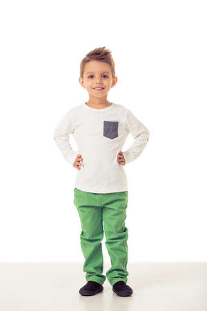 akimbo: Full length portrait of cute little boy in stylish clothes looking at camera and smiling while standing akimbo, isolated on a white background Stock Photo