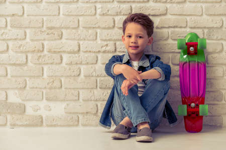 Stylish little boy in jeans clothes is looking at camera and smiling, sitting against white brick wall
