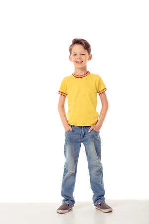 Retrato de cuerpo entero de niño pequeño divertido mirando a cámara y sonriendo mientras está de pie con las manos en los bolsillos, aislado en un fondo blanco Foto de archivo