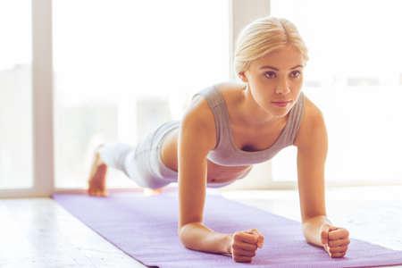 Schöne junge Frau in Sportbekleidung tun Plank Übung auf Yoga-Matte