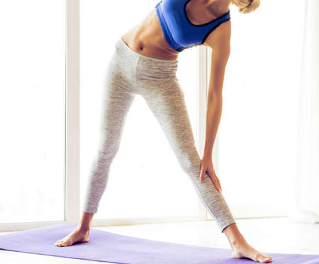 cropped image: Cropped image of beautiful young woman in sports wear doing yoga on mat against windows