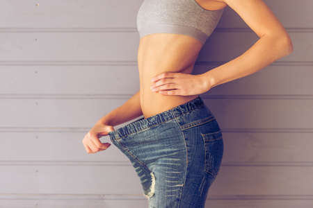pulling beautiful: Side view of beautiful young slim woman pulling her jeans showing loss of weight, on a gray background, cropped