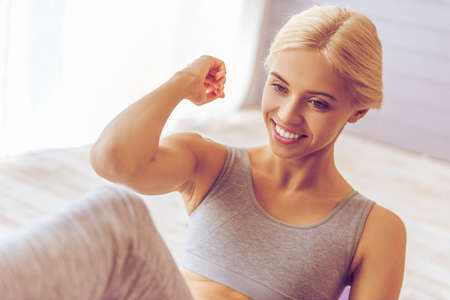 cropped out: Cropped image of beautiful young woman in sports wear smiling while working out