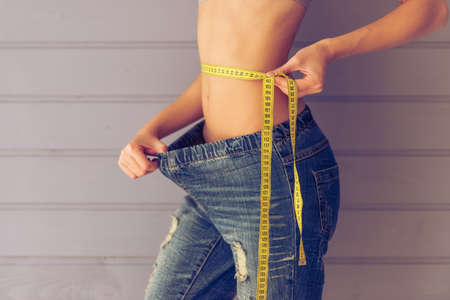 pulling beautiful: Cropped image of beautiful young slim woman pulling her jeans and using a tape measure showing loss of weight, on a gray background