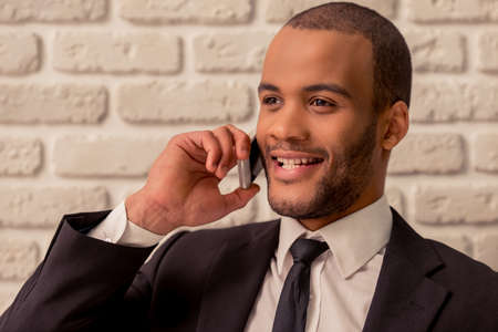 american banker: Portrait of handsome Afro American businessman in classic suit talking on the mobile phone and smiling, against white brick wall Stock Photo