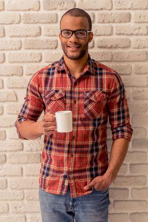 カメラ目線や笑顔、白いレンガの壁に、カジュアルな服装と眼鏡のハンサムなアフロ アメリカ男が飲み物のカップを保持しています。