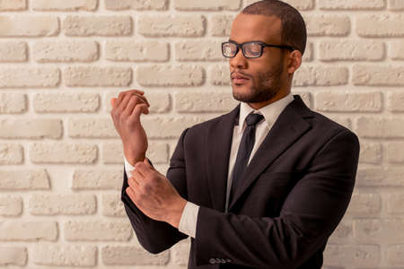 young  cuffs: Handsome Afro American businessman in classic suit and eyeglasses is adjusting his cuff, against white brick wall Stock Photo