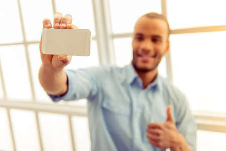 business man phone: Handsome Afro American man in casual clothes is making selfie using a smart phone, showing Ok sign and smiling. Phone in focus