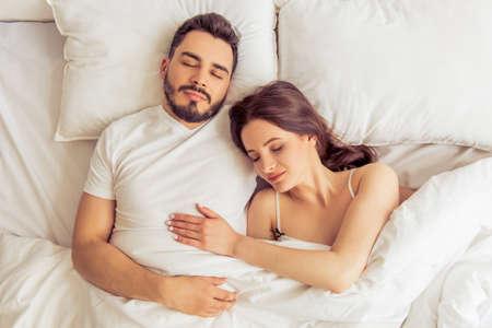 pareja durmiendo: Vista superior de la hermosa mujer joven y su hombre abrazando mientras duerme en cama en su casa