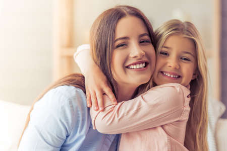 Portrait of beautiful young mother and her daughter hugging, looking at camera and smiling