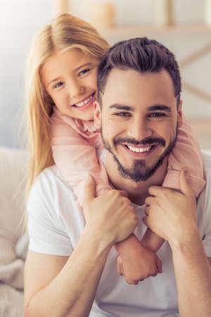 ハンサムな父親とハグ、カメラを見て、自宅のソファに腰掛けながら笑顔のかわいい娘の肖像画