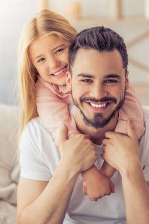 Portrait of handsome father and his cute daughter hugging, looking at camera and smiling while sitting on sofa at home Banque d'images